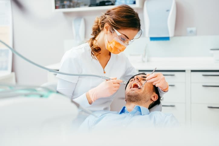 Female dentist working on patient's teeth.